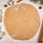 Gingerbread cookies dough preparation recipe with man shape, fir trees, snowman and star forms, cinnamon rolling pin, flour on white kitchen table. Traditional homemade christmas dessert